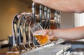 stock photo of bartender  - Mans hand pouring pint of beer behind the bar - JPG