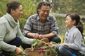 image of granddaughter  - Grandparents and granddaughter in garden - JPG
