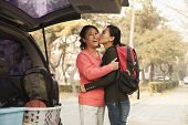 stock photo of ponytail  - Mother and daughter embracing behind car on college campus - JPG