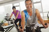 picture of exercise bike  - Man smiling and exercising on the exercise bike - JPG