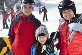 pic of family ski vacation  - Family Smiling in Ski Resort - JPG
