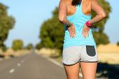 stock photo of muscle strain  - Female runner athlete low back injury and pain - JPG
