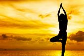 stock photo of natarajasana  - Woman doing yoga at sunset time - JPG