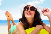 stock photo of sunbathing woman  - Woman wearing sunglasses and a hat - JPG