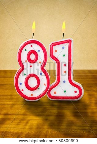 Burning birthday candles number 81 on a wooden background