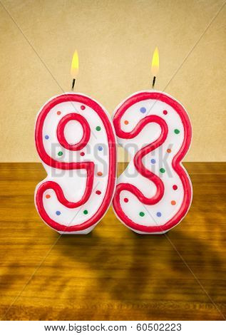 Burning birthday candles number 93 on a wooden background