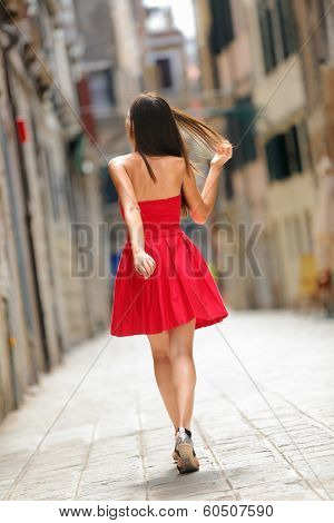 Woman in red dress walking in street in Venice, Italy cheerful and happy in rear view showing back of sundress. Pretty sexy brunette fashion model girl in her 20s.