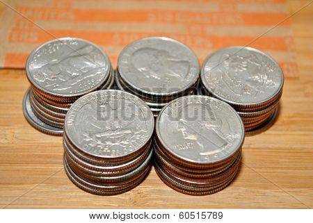 Stacked Quarters with a Paper Bank Roller Behind Them