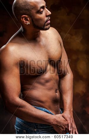 naked man with perfect body posing in jeans