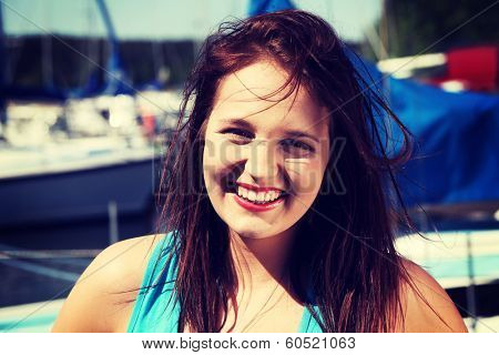 Beautiful young woman with dispelled hair in yacht harbor. Happy girl in front of yacht boat.