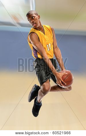 African American basketball player dunking ball over blurred background