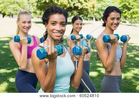 Group portrait of confident sporty women lifting hands weights in park