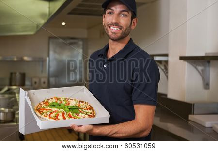 Happy pizza delivery man showing fresh pizza in a commercial kitchen