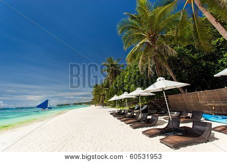 Sun Umbrellas And Beach Chairs On Tropical Coastline