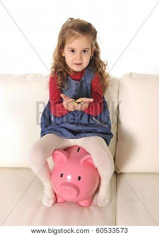 Happy Cute Little Girl Sitting On Huge Piggy Bank Holding Coins