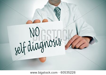 a man wearing a white coat sitting in a desk holding a signboard with the text no self diagnosis written in it