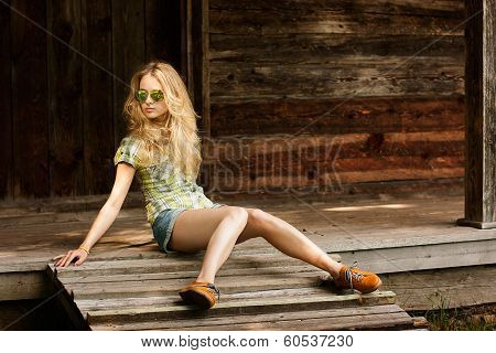Trendy Hipster Girl Sitting on the Wooden Porch
