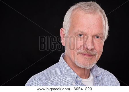 Senior man in front of black background