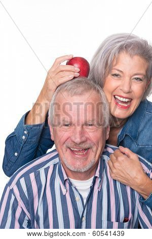 Senior couple with apple in front of white background