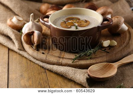 Composition with mushroom soup in pot, fresh and dried mushrooms, on wooden table, on sackcloth background