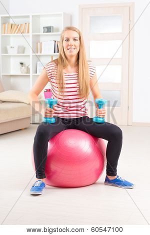 Beautiful young woman with gym ball and dumb bells exercising.