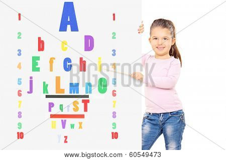Young child pointing on a colorful eyesight test with a wooden stick isolated on white background