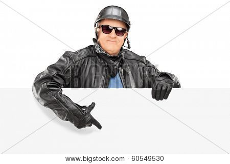 Mature biker pointing on a blank panel isolated on white background
