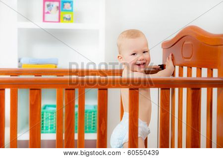 Baby boy standing in crib at home