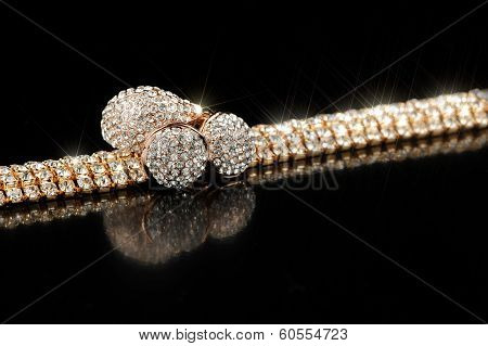 Gold Earrings, Bracelet And Ring With Shiny Stones On Black Background