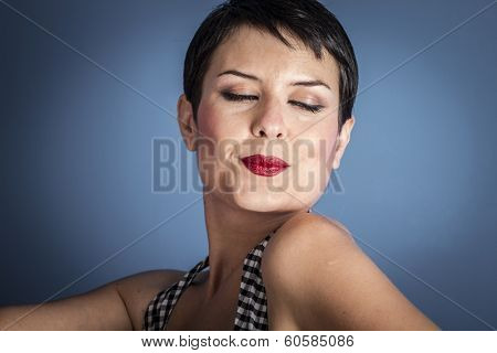happy young woman with lollypop  in her mouth on blue background