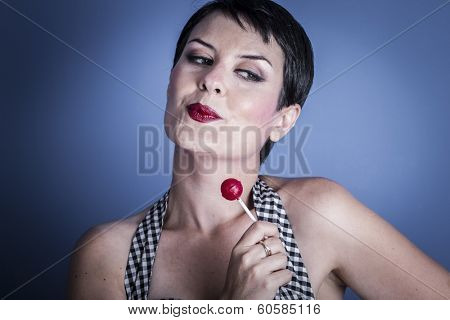 Sexy happy young woman with lollypop  in her mouth on blue background