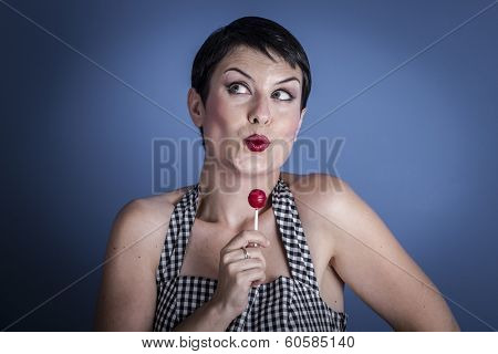 Lolly, happy young woman with lollypop  in her mouth on blue background