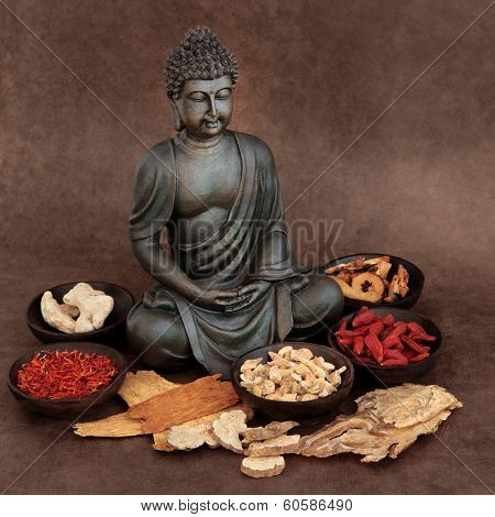 Chinese herbal medicine selection with buddha over handmade lokta paper background.