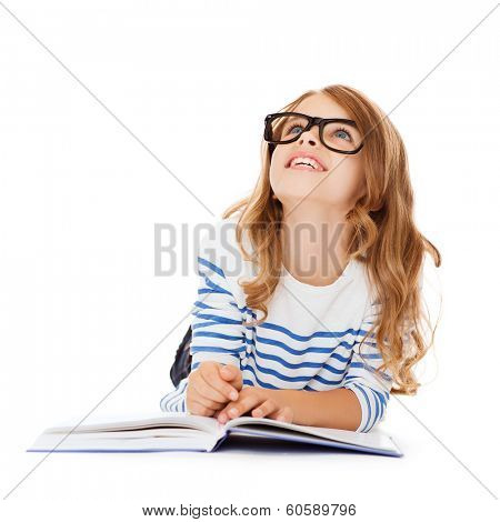 education and school concept - smiling little student girl with book and eyeglasses lying on the floor and looking up