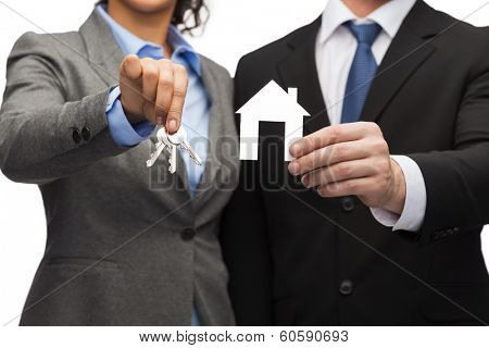 business, eco, real estate and office concept - businessman and businesswoman holding white paper house and keys
