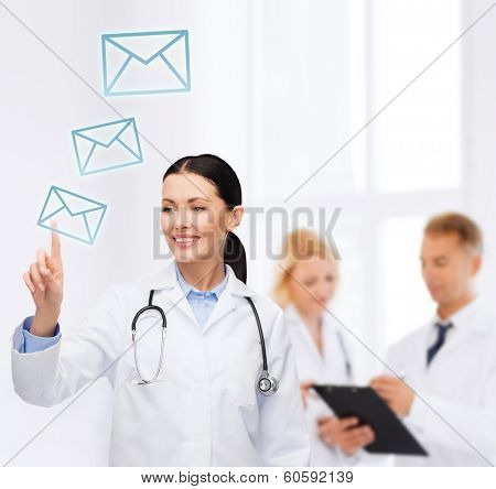 healthcare, medicine and technology concept - smiling female doctor with stethoscope pointing to envelope