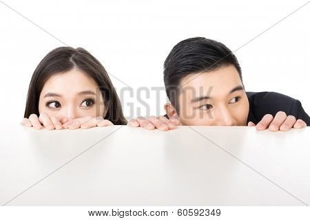 Asian business man and woman hide under the table and looking somewhere.