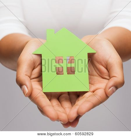 real estate and eco concept - closeup picture of woman hands holding green house