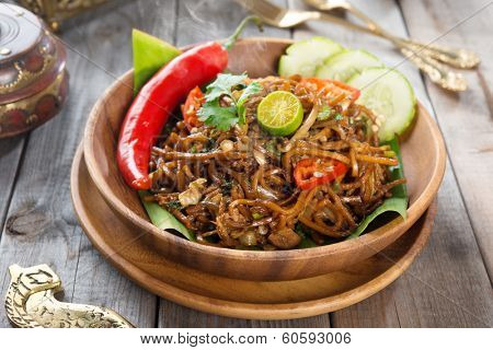 Mi goreng or mee goreng mamak, Indonesian and Malaysian cuisine, spicy fried noodles with wooden dining table setting. Fresh hot with steamed smoke.