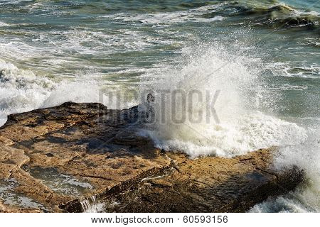 Waves Breaking On The Rocks.