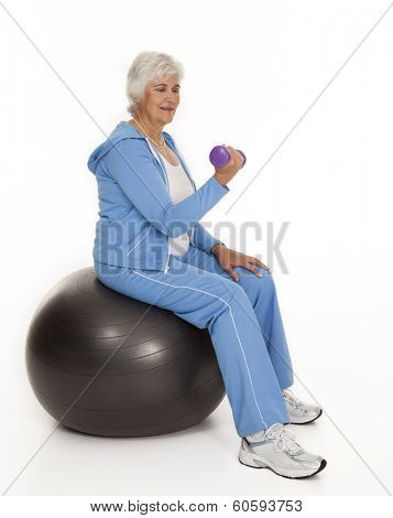 Female senior citizen seated on exercise ball lifting dumbbell on white background.