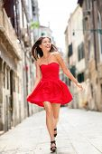 Happy beautiful woman in red summer dress walking and running joyful and cheerful smiling in Venice,
