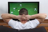 stock photo of sofa  - Young man sitting on a sofa and watching football or soccer on tv - JPG
