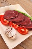 stock photo of flank steak  - fresh raw beef meat steak fillet on wooden plate with asparagus and tomatoes ready to prepare - JPG
