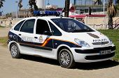 Police car by beach, Malaga, Spain.