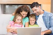 Happy family sitting on sofa using laptop together at home in living room