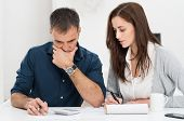 foto of family planning  - Portrait Of A Worried Couple Calculating Financial Budget - JPG