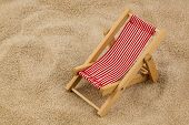 a small deck chair (model) on a sandy beach. symbolic photo for vacation, holiday, travel