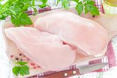 stock photo of fowl  - Fresh raw chicken breast on a chopping board - JPG