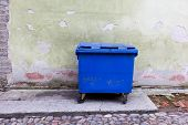 pic of dumpster  - Blue dumpster against a bright green wall cleaning and recycling in city - JPG